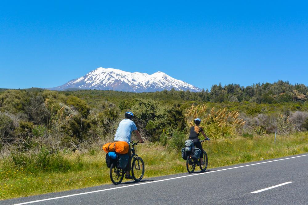 Casal viaja de bicicleta pela estrada